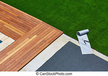 Artificial grass installation in deck garden with tools -...