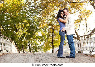 Smile Engagement Couple - A happy couple in the park looking...