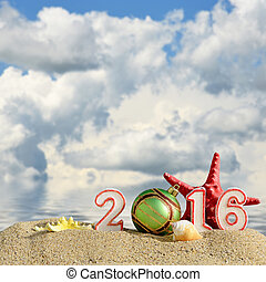Christmas background with New year 2016 sign on a beach sand