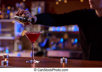 Cocktail shaker and a bartender - Bartender is using a...