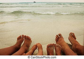 Family feet on the sand on the beach - a Family feet on the...