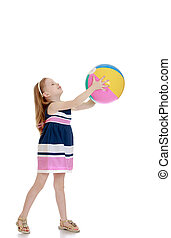 Little girl holding a beach ball in his outstretched hands