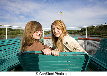 teenage girls sitting on a river shipboat