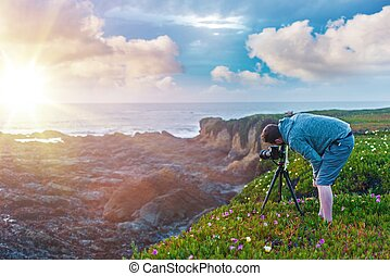 Nature Photography. Photographer on the Ocean Cliff Taking...