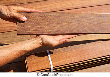 Ipe deck installation carpenter hands holding wood - Ipe...