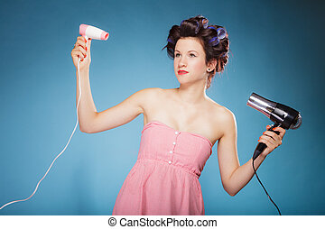 girl with curlers in hair holds hairdreyers - Young woman...