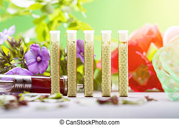 small glass tubes with homeopathy globules, syringe and...