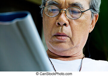 Senior man relaxing at home reading E-book on his tablet