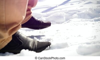 Slow motion of Man trekking in snow, sunny winter day