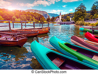 Bohinj Lake with boats and Church of St John the Baptist,...