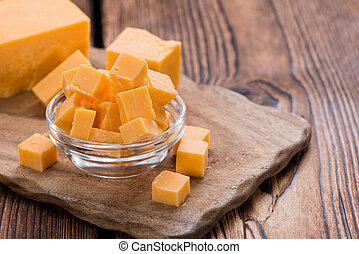 Cheddar - Pieces of Cheddar close-up shot on an old wooden...