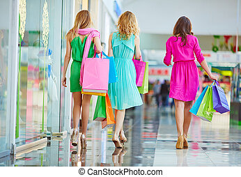 Backs of shoppers - Group of shoppers carrying paperbags