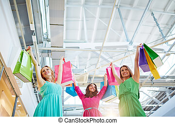 Joyful consumers - Satisfied shopaholics with paperbags in...