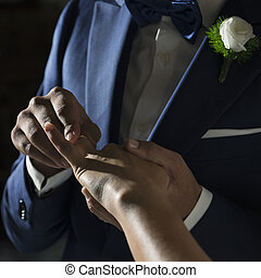 wedding ring - Details of a husband that is putting wedding...