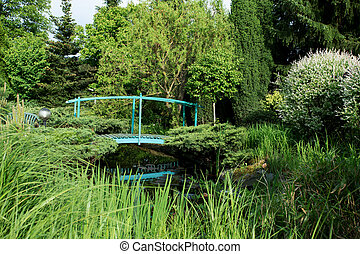 small green footbridge over a pond on spring garden