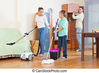 Couple and boy vacuuming together - Happy couple and...