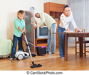 Cleaning at home - Adult couple with teenage son doing house...