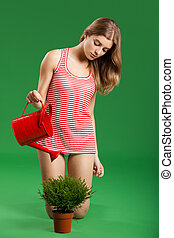 Female young gardener - Young female gardener over a green...
