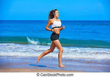 Beautiful brunette girl running in a summer beach -...