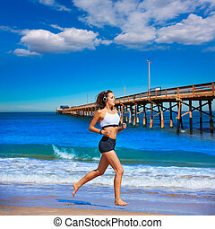 Beautiful brunette girl running in California beach photo...