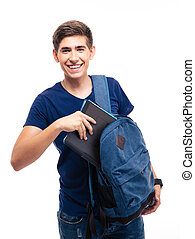 Male student putting folder in backpack - Smiling male...