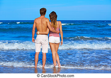 Young couple standing looking at the beach rear