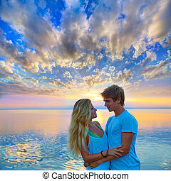 Blond young couple hug in sunset sea lake happy