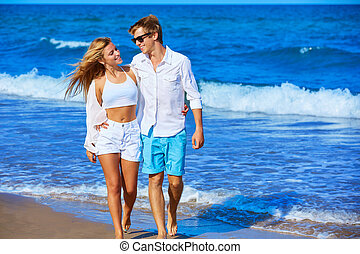 Blond young couple walking in the beach shore