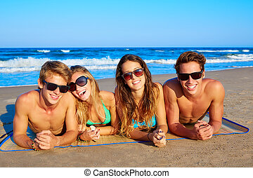 Group of young friends couples portrait in beach lying on...