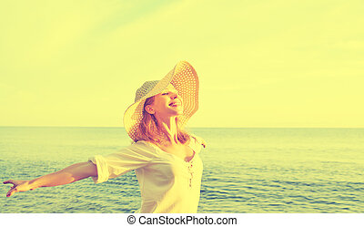 Happy beauty woman in hat opened his hands, enjoys sunset...