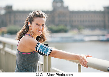 Smiling woman in workout gear listening to music by city...