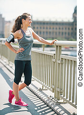 Smiling woman in workout gear standing on a bridge - An...