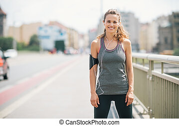 Smiling woman jogger standing still on bridge - A woman is...