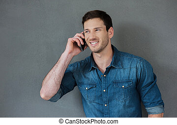Good talk with friend. Cheerful young man talking on the mobile phone and smiling while standing against grey background