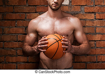 Ready to play ball. Cropped image of young muscular man...