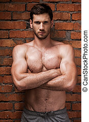Strong man. Confident young muscular man keeping arms...