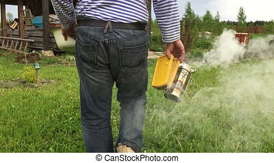 Beekeeper and smoker - Man walks with a smoker for bees