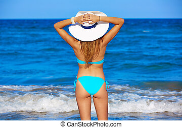 Girl young standing looking at the sea beach hat