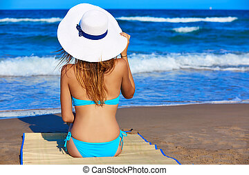 Girl young sitting looking at the sea with beach hat rear...
