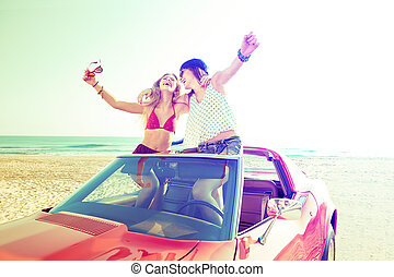 Beautiful party girls dancing in a car on the beach -...