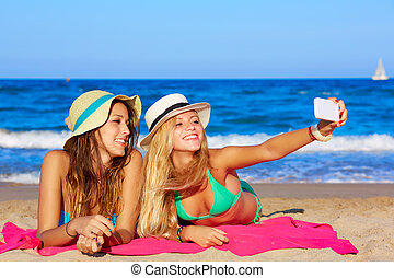 happy girl friends selfie portrait lying on beach sand in...