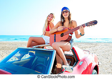 girls having fun playing guitar on th beach in a car - girls...
