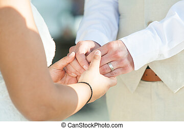 Bride and groom holding hands outdoors in wedding ceremony