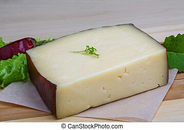 Hard cheese on the wood background with salad leaves