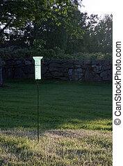 Plastic green rain-gauge in sunny garden