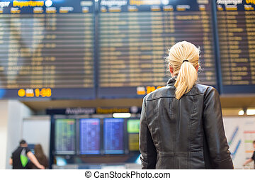 Female traveller checking flight departures board. -...