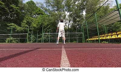 Man playing badminton on court
