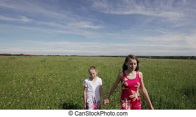 Young girl running in a field holding hands - sisters...