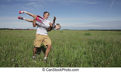 father playing with his daughter in field - Father holds...