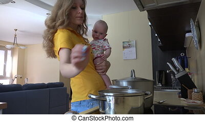 woman hold baby kitchen - Pretty woman in yellow holding...